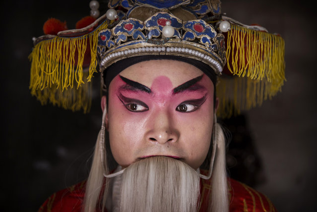 Sichuan Opera performer Wu Yonghong, 26 years, of the Jinyuan Opera Company prepares backstage before performing for villagers at the Dongyue Temple on May 2, 2016 in Cangshan, Sichuan province, China. (Photo by Kevin Frayer/Getty Images)
