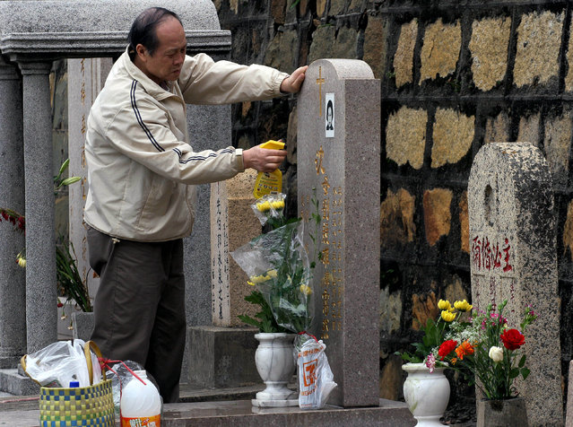 A man cleans the grave of a relative during the Qing Ming or Ching ming festival in Hong kong, 05 April 2007. Chinese around the world visit graves to pay respect to their ancestors in the buildup to the traditional Ching Ming festival. (Photo by Woody Wu/AFP Photo)
