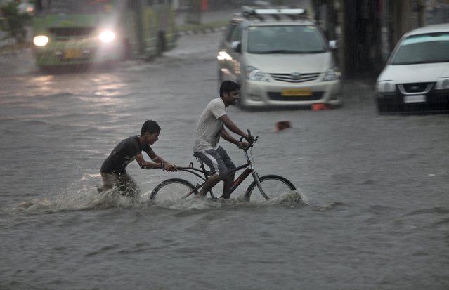 An Indian man pedals a cycle as a boy pushes it through a flooded street during a monsoon shower in Jammu, India, Monday, June 29, 2015. Heavy rains lashed the city bringing much needed relief from the scorching heat wave. (Photo by Channi Anand/AP Photo)