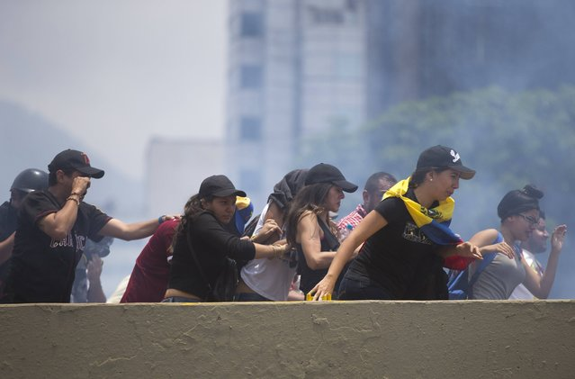 Demonstrators run away from tear gas, launched by the Bolivarian National Police during a protest in Caracas, Venezuela, Monday, April 10, 2017. Opponents of President Nicolas Maduro protested on the streets of the capital as part of an ongoing protest movement that shows little sign of losing steam. (Photo by Ariana Cubillos/AP Photo)