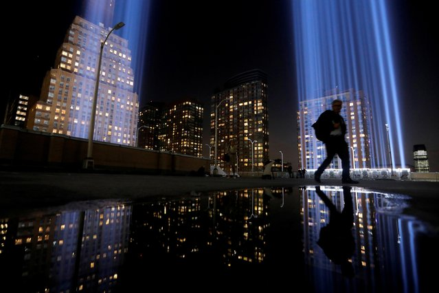 A man walks by the Tribute in Light, lit to commemorate the 18th anniversary of September 11, 2001 attacks in New York City, U.S., September 10, 2019. (Photo by Andrew Kelly/Reuters)