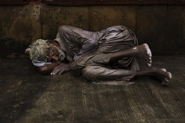 An Indian homeless man tries to sleep on a wet street during monsoon rains in New Delhi, India, Saturday, July 11, 2015. (Photo by Bernat Armangue/AP Photo)