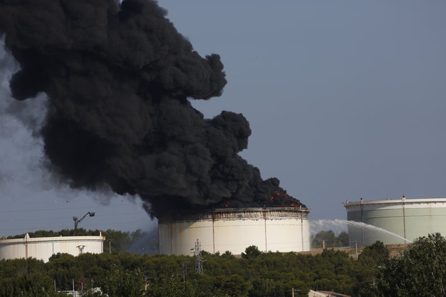 The smoke spreads in the sky from a fire in a tank of the U.S. Lyondellbasell chemicals group refinery, in Berre l'Etang, southern France, Tuesday, July 14, 2015. Two parallel explosions have rocked tanks at a chemical plant near Marseille Provence Airport . Authorities have launched an inquiry into the incident which occurred Tuesday morning as the country began celebrations for its national Bastille Day. (Photo by AP Photo/Stringer)