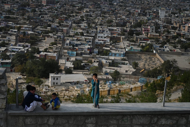 Children react as they sit on a path at Wazir Akbar Khan hilltop overlooking Kabul on September 29, 2019. Voter participation in Afghanistan's presidential elections appeared on September 29 to have been lower than in previous years, with turnout hit by the threat of attacks, a muted campaign and concerns of fraud. Afghans went to the polls on September 28 to vote in the first round of a presidential race that will decide whether President Ashraf Ghani will win a second five-year term. (Photo by Sajjad Hussain/AFP Photo)
