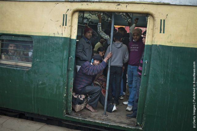 Men look out from a carriage train as it leaves from the Nizamuddin Railway Station in New Delhi, India