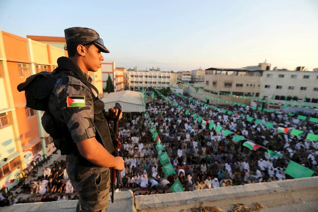 A member of Palestinian security forces loyal to Hamas stands guard as Palestinians perform morning prayers of Eid al-Fitr holiday, marking the end of the holy month of Ramadan, in the east of Gaza City July 17, 2015. (Photo by Ibraheem Abu Mustafa/Reuters)