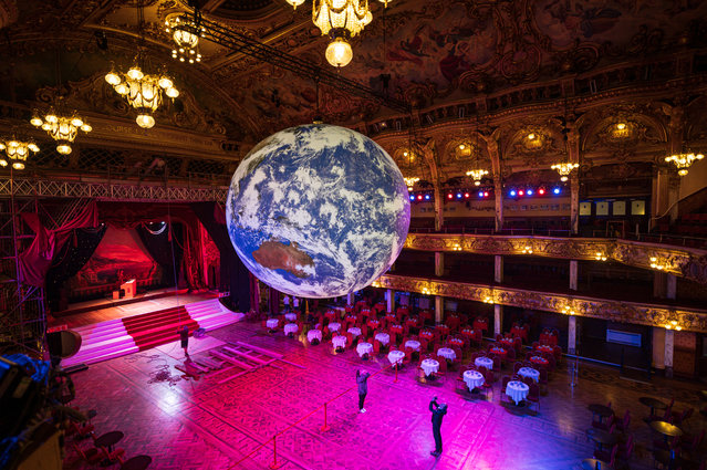 "Members of the public admire an illuminated art installation entitled ""Gaia"" by artist Luke Jerram in the Blackpool Tower Ballroom, as part of the Lightpool Festival of visual arts in the centre of Blackpool, northern England on October 14, 2019. The annual festival, which runs until October 26, 21019, features a mix of live performance and light-based art installations at various locations throughout the town. The annual festival, which runs until October 26, 21019, features a mix of live performance and light-based art installations at various locations throughout the town. (Photo by Oli Scarff/AFP Photo)"