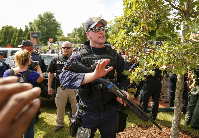 A South Carolina State Trooper yells for protesters to get back after a member of the Ku Klux Klan crashed into a light pole while leaving a rally at the statehouse in Columbia, South Carolina July 18, 2015. (Photo by Chris Keane/Reuters)