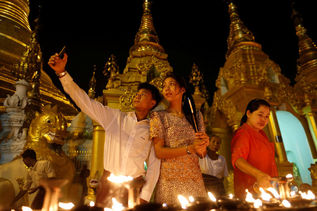 A family takes a seflie as they visit the Shwedagon Pagoda during Kason Watering Festival celebrations, also know as Vesak Day, in Yangon, Myanmar May 10, 2017. (Photo by Soe Zeya Tun/Reuters)