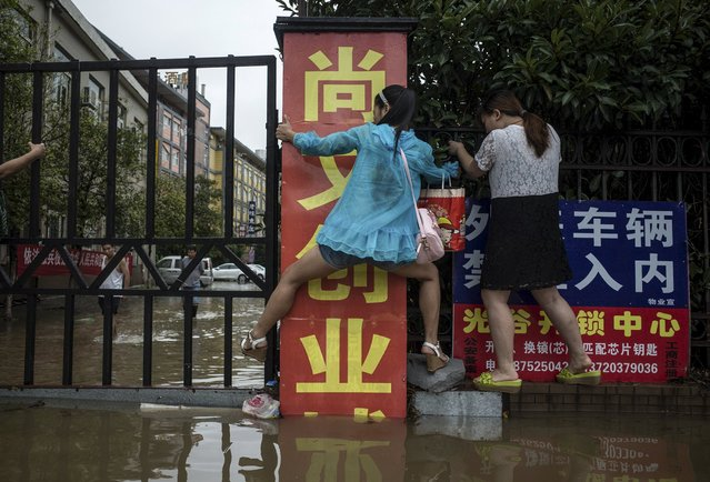 Residents make their way along a fence as they try to cross a flooded street after heavy rainfall hit Wuhan, Hubei province, China, July 23, 2015. (Photo by Reuters/China Daily)
