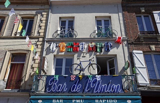 Bicycles and cycling jerseys hang outside a cafe at the start of the 7th stage of the 102nd Tour de France cycling race from Livarot to Fougeres, France, July 10, 2015. (Photo by Eric Gaillard/Reuters)