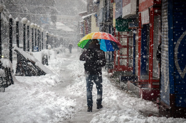A resident walks through heavy snowfall in the Kashmiri city, India on November 11, 2019. There have been several fatalities as the winter weather arrives in the region. (Photo by Saqib Majeed/Barcroft Media)