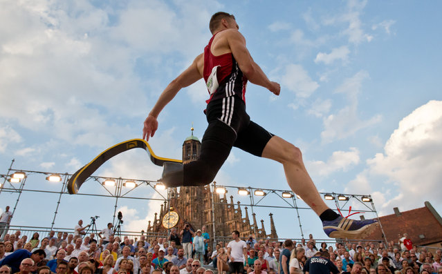 Paralympic champion Markus Rehm makes an attempt in the long jump competition at the German Championships in Nuremberg, Germany, Saturday, July 25, 2015. Jumping on a specially constructed pit in a city square, Rehm won the competition with an effort of 8.11 meters. (Photo by Daniel Karmann/dpa via AP Photo)