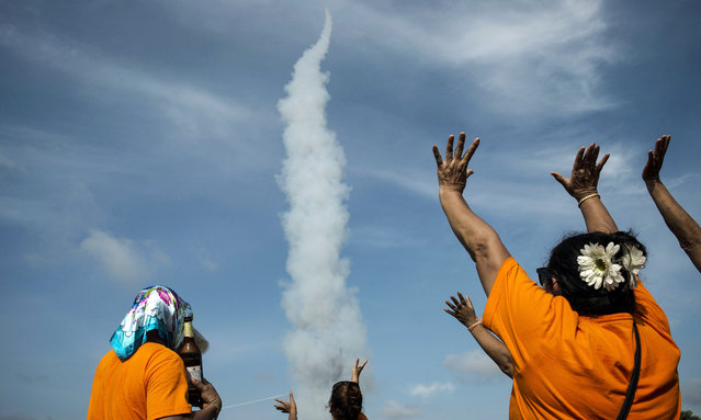 In this photograph taken on May 29, 2016, people celebrate as a homemade rocket is launched during the annual Rocket Festival in the village of Houa Xeing on the outskirts of Vientiane. In central Laos dozens of loud explosions pockmark the sky as men dressed in female clothing wielding large wooden phalluses dance, while others lubricated by the local rice whiskey simply roll in the mud. (Photo by Lillian Suwanrumpha/AFP Photo)