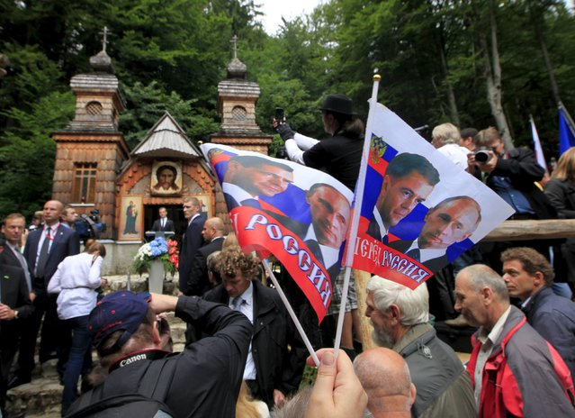 People wave flags depicting images of Russian Prime Minister Dmitry Medvedev and President Vladimir Putin during the commemoration of the Russian Chapel in Vrsic, Slovenia July 26, 2015. (Photo by Srdjan Zivulovic/Reuters)