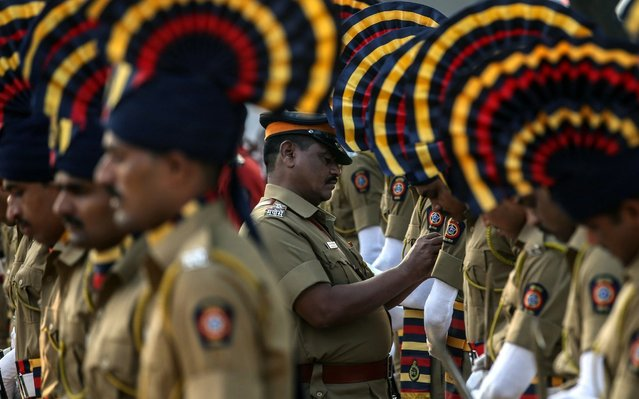 Indian police personnel adjust their clothing before paying tribute to victims on the eleventh anniversary of the 2008 Mumbai Terror Attacks, in Mumbai, India, 26 November 2019. More than 160 people were killed and over 300 others were injured in Mumbai on 26 November 2008, when 10 heavily-armed Islamist militants attacked a number of sites including, two luxury hotels, the Taj Mahal Palace, Oberoi hotel, Leopold cafe and a Jewish center Chabad House. (Photo by Divyakant Solanki/EPA/EFE)