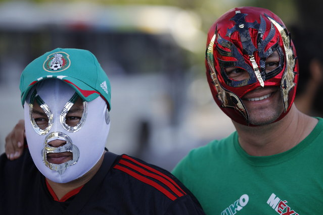Mexican soccer fans pose for the photo wearing wrestling masks in front of Maracana stadium, in Rio de Janeiro, Brazil, Wednesday, June 11, 2014. The World Cup soccer tournament starts Thursday. (Photo by Leo Correa/AP Photo)