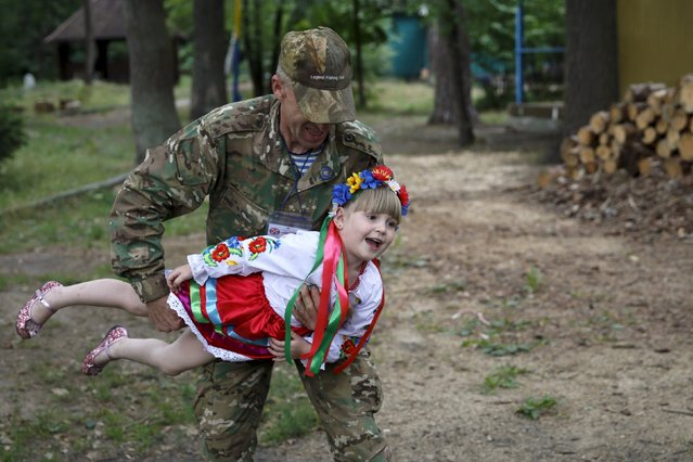 A security personnel plays with a girl in the compound of a health and rest centre which serves as a temporary accommodation for refugees from eastern regions of the country in the town of Korostyshiv, Zhytomyr region, Ukraine, July 30, 2015. (Photo by Valentyn Ogirenko/Reuters)