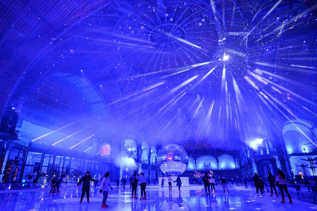 People skate on the ice skating rink hosted at the glass-roofed central hall of the Grand Palais in Paris, on December 17, 2019. (Photo by Thomas Samson/AFP Photo)