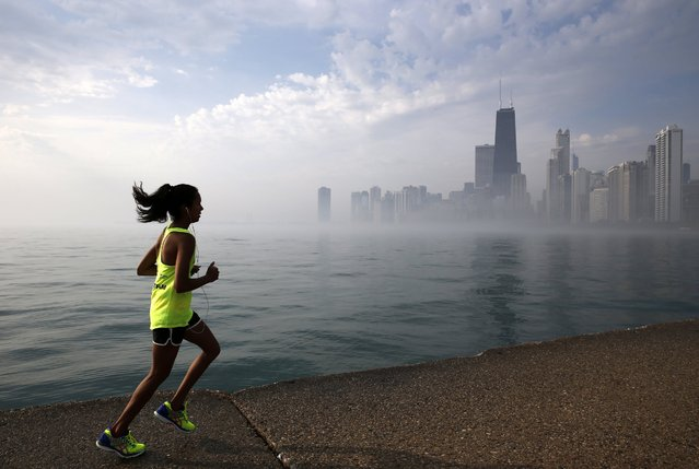 A runner jogs along the shore of Lake Michigan as morning fog covers the downtown skyline, Friday, June 10, 2016, in Chicago. (Photo by Kiichiro Sato/AP Photo)