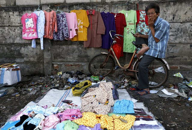 A man selling clothes smokes a cigarette while waiting costumers near Duri train station in Jakarta, Indonesia August 3, 2015. Indonesia's economic growth is expected to have slowed in the second quarter to the weakest level in nearly six years, despite the government's promise to jumpstart the economy after a dismal first quarter. (Photo by Reuters/Beawiharta)