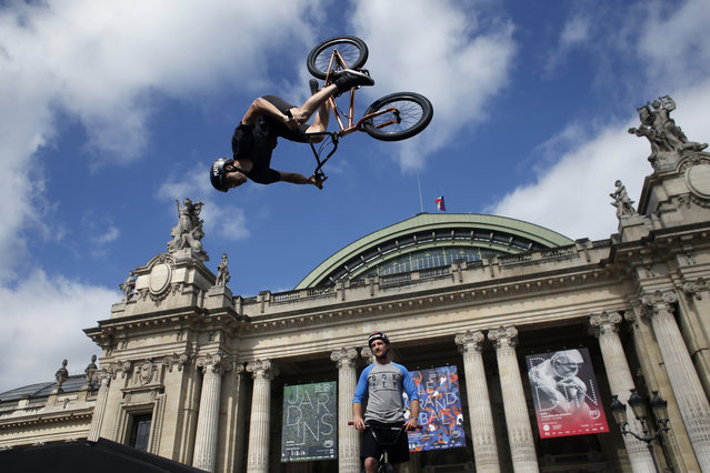 Belgian biker Kenneth Tancre performs outside the Grand Palais museum in Paris, Friday, June 23, 2017. Paris is aiming to boost its bid for the 2024 Olympics by turning some of its world-famous landmarks over to sports for two days, with 100-meter races on a track floating on the Seine, high-diving into the river, cycling around the Arc de Triomphe and other events to showcase the French capital's suitability for the games. (Photo by Thibault Camus/AP Photo)