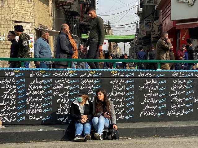 Women sit by a wall with names of Anti-government protesters who have been killed in demonstrations in Tahrir Square during ongoing protests in Baghdad, Iraq, Thursday, December 12, 2019. A gunman shot dead several people, including four protesters, Thursday provoking some anti-government demonstrators to disarm and hang him in a central Baghdad square, security and health officials said. The incident was condemned by the wider protest movement based in Tahrir Square, the epicenter of the movement, who said the individuals who killed the gunman were not part of their peaceful demonstrations. (Photo by Khalid Mohammed/AP Photo)