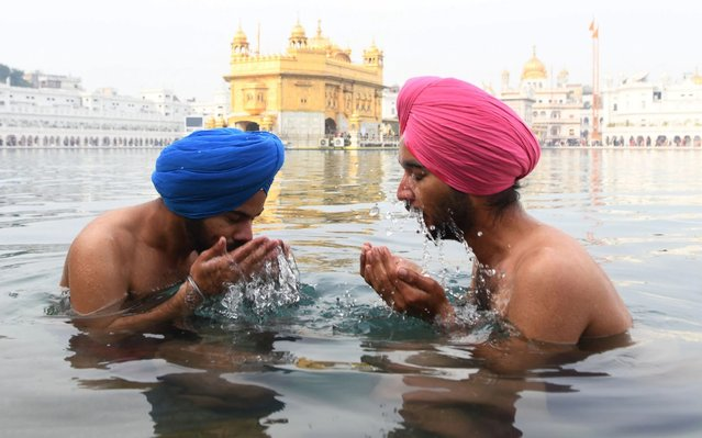 Sikh devotees take a dip in the holy sarovar (water tank) on the occasion of the birth anniversary of the 10th Sikh Guru Gobind Singh at the Golden Temple in Amritsar on January 2, 2020. (Photo by Narinder Nanu/AFP Photo)