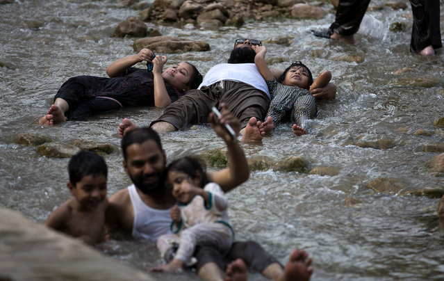 People cool themselves at a stream in suburbs of Islamabad to beat the heat as temperatures reached 40 Celsius (104F) in Islamabad during the holy fasting month of Ramadan, June 14, 2016 in Pakistan. Muslims across the world refrain from eating, drinking and smoking from dawn to dusk during the month of Ramadan. (Photo by B.K. Bangash/AP Photo)