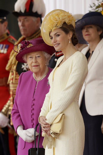 Britain's Queen Elizabeth II stands with Spain's Queen Letizia as their husbands King Felipe and Prince Philip inspect an honour guard during a Ceremonial Welcome on Horse Guards Parade in London, Wednesday, July 12, 2017. The King and Queen of Spain are on a three day State Visit to Britain. (Photo by Matt Dunham/AP Photo)