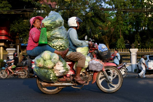 A woman holds piles of vegetables transported by motorcycle along a street in Phnom Penh, Cambodia on January 22, 2020. (Photo by Tang Chhin Sothy/AFP Photo)