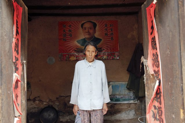 """Chinese former """"comfort woman"""" Ren Lane poses in front of a poster of China's late Chairman Mao Zedong pasted on the wall of a room that is not in use at her house in Gucheng Town, Shanxi Province, China, July 17, 2015. (Photo by Kim Kyung-Hoon/Reuters)"""