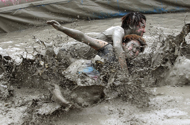 Men wrestle in a mud pool during the Boryeong Mud Festival at Daecheon Beach in Boryeong, South Korea, Friday, July 18, 2014. The 17th annual mud festival features mud wrestling and mud sliding. (Photo by Ahn Young-joon/AP Photo)