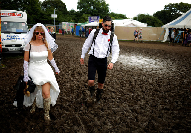 Revellers walk in the mud at Worthy Farm in Somerset during the Glastonbury Festival, Britain, June 26, 2016. (Photo by Stoyan Nenov/Reuters)