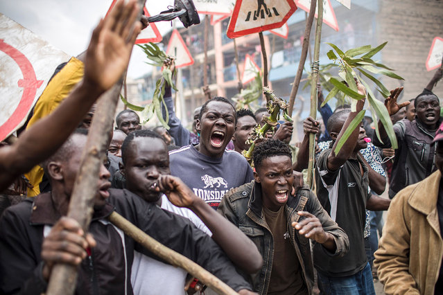 Supporters of the Kenyan opposition presidential candidate shout and hold sticks during a protest in the Mathare slums of Nairobi on August 9, 2017, a day after the presidential election. President Uhuru Kenyatta appeared headed for re-election on August 9 but his rival Raila Odinga claimed a massive hacking attack had manipulated results, ratcheting up tensions in opposition strongholds. (Photo by Luis Tato/AFP Photo)