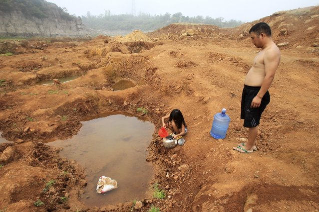 A girl collects water from a puddle at a dried-up reservoir as her father stands beside her in Baofeng county, Henan province July 30, 2014. Lingering droughts in most parts of China have affected millions of hectares of agricultural crops, the State Flood Control and Drought Relief Headquarters said on Wednesday. (Photo by Reuters/Stringer)
