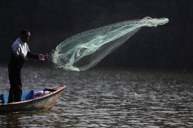 Nepalese man Bhakta Bahadur Gurung throws a fishing net to catch fish in Phewa Lake in Pokhara, Nepal, Thursday, January 2, 2020. Phewa Lake is one among seven lakes in Pokhara. (Photo by Niranjan Shrestha/AP Photo)