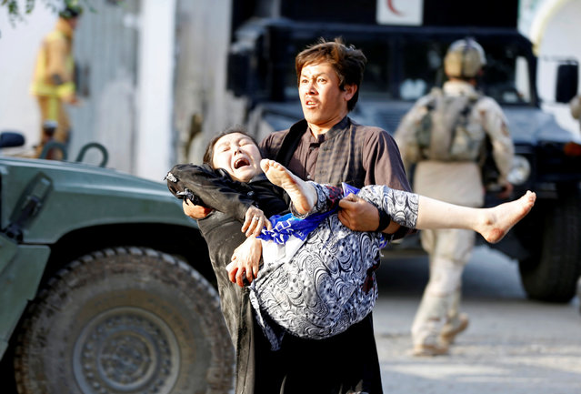 An Afghan man carries an injured woman from the site of a suicide attack followed by a clash between Afghan forces and insurgents after an attack on a Shi'ite Muslim mosque in Kabul, Afghanistan on Friday, August 25, 2017. (Photo by Omar Sobhani/Reuters)