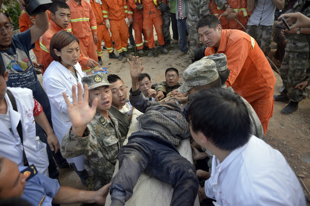 In this photo taken Tuesday, Aug. 5, 2014, earthquake survivor Xiong Zhengfen, 88, is evacuated by rescue workers after being buried under rubble for 50 hours in Ludian county in southwest China's Yunnan province. Some 10,000 troops and hundreds of volunteers have rushed to Ludian to clear roads and dig out possible survivors from the debris following Sunday's quake , but landslides and bouts of heavy rains have complicated rescue efforts. (Photo by AP Photo)