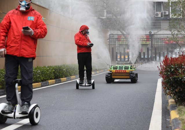 Workers ride smart self-balancing scooters as they control a robotic sprayer spraying disinfectant at a residential compound in Wuhan, China, March 3, 2020. (Photo by Reuters/China Daily)