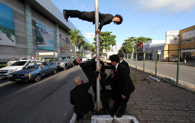 "Members of the dance company ""Gentlemen de Rua"" (GRua), or ""Gentlemen of the Street"", hold their street performance titled ""Body Passing"" on the streets of Natal, August 8, 2014. The GRua dancers, based in Sao Paulo, are in Natal for a national gathering of contemporary dance. (Photo by Nuno Guimaraes/Reuters)"