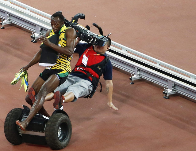 A TV cameraman drives into Usain Bolt of Jamaica after the men's 200m final during the Beijing 2015 IAAF World Championships at the National Stadium, also known as Bird's Nest, in Beijing, China, 27 August 2015. Bolt won the race. (Photo by Rolex Dela Pena/EPA)