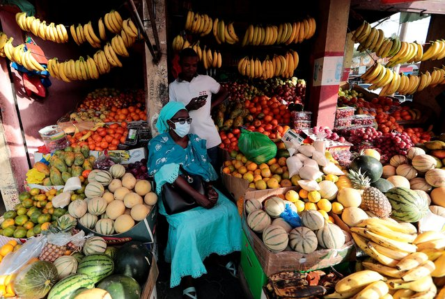 A woman wears a protective face mask, due to the global coronavirus disease (COVID-19) outbreak, as she waits to get her change after buying fruits in Dakar, Senegal on March 18, 2020. (Photo by Zohra Bensemra/Reuters)