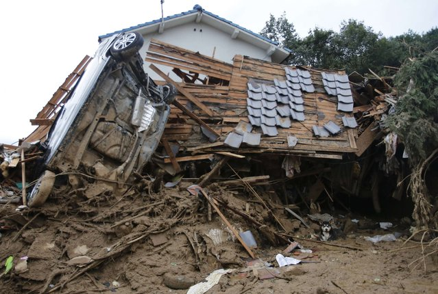 A dog takes a rest under a destroyed house at a site where a landslide swept through a residential area at Asaminami ward in Hiroshima, western Japan, August 20, 2014. At least 36 people, including several children, were killed in Japan on Wednesday, when landslides triggered by torrential rain slammed into the outskirts of the western city of Hiroshima, and the toll could rise further, police said. (Photo by Toru Hanai/Reuters)