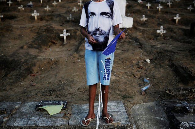 A boy holds his kite before flying it in a cemetery in the Vila Operaria Favela of Rio de Janeiro, Brazil, July 9, 2016. (Photo by Nacho Doce/Reuters)