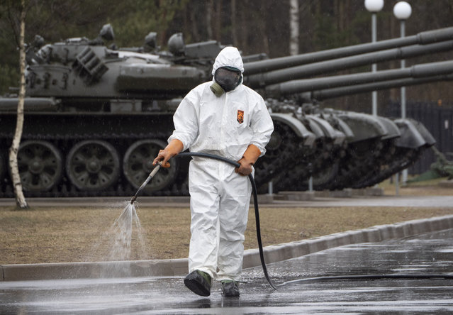 A specialist from a local veterinary service wears a protective suit as sprays disinfectant near Russian tanks displayed at area near Proryv (The Breakthrough) museum dedicated to the breakthrough of the Siege of Leningrad during World WarII near Kirovsk, about 30 kilometres (19 miles) east of St.Petersburg, Russia, Thursday, April 2, 2020. (Photo by Dmitri Lovetsky/AP Photo)