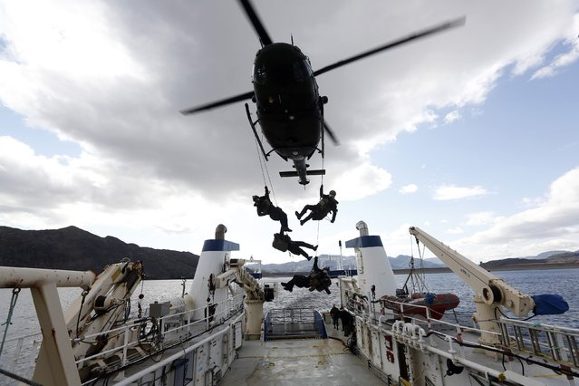Members of the Canadian Joint Incident Response Unit rappel from a Griffon helicopter on to a ship while taking part in a scenario during the Operation Nanook military exercise on Baffin Island, Nunavut August 26, 2014. (Photo by Chris Wattie/Reuters)