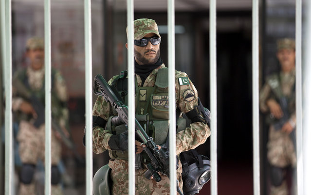 Pakistani army soldiers stand alert inside the parliament building during an emergency session in Islamabad, Pakistan, Tuesday, September 2, 2014. Lawmakers met over the political crisis roiling the country as thousands of anti-government protesters remained camped out in front of the parliament building, demanding Prime Minister Nawaz Sharif resign. (Photo by B. K. Bangash/AP Photo)