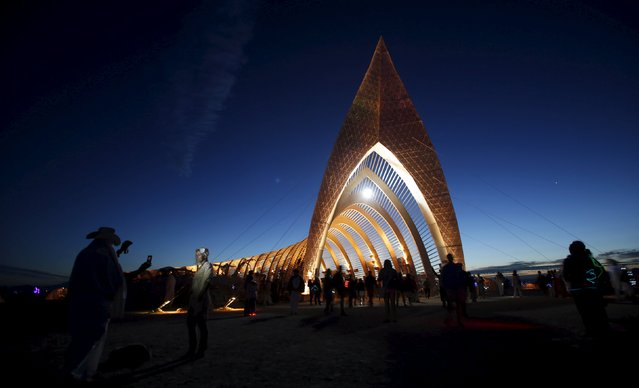 """People gather before sunrise at the Temple of Promise during the Burning Man 2015 """"Carnival of Mirrors"""" arts and music festival in the Black Rock Desert of Nevada, September 3, 2015. (Photo by Jim Urquhart/Reuters)"""