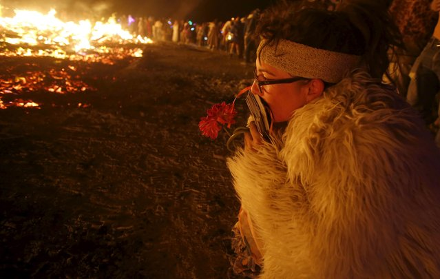 """KT Cubb kneels at the burning remains of the Temple of Promise during the Burning Man 2015 """"Carnival of Mirrors"""" arts and music festival in the Black Rock Desert of Nevada, September 6, 2015. (Photo by Jim Urquhart/Reuters)"""